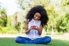 Fille noire adolescente à l'aide d'un téléphone, se trouvant sur l'herbe - p africain Photographie stock