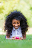 Fille noire adolescente à l'aide d'un téléphone, se trouvant sur l'herbe Photos stock