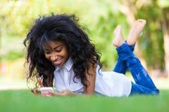 Fille noire adolescente à l'aide d'un téléphone, se trouvant sur l'herbe - p africain Photo stock