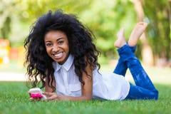 Fille noire adolescente à l'aide d'un téléphone, se trouvant sur l'herbe - p africain Photos stock