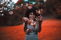 Fille noire jetant les feuilles d'automne sèches en parc photos libres de droits