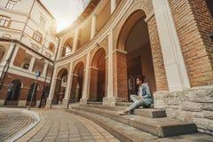 Fille noire s'asseyant sur l'escalier dans les environnements urbains image stock