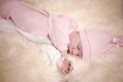 Fille nouveau-née dans une robe rose dormant sur la peau de moutons Photographie stock libre de droits
