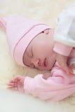 Fille nouveau-née dans une robe rose dormant sur la peau de moutons Photos libres de droits