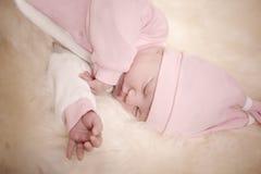 Fille nouveau-née dans une robe rose dormant sur la peau de moutons Images stock