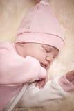 Fille nouveau-née dans une robe rose dormant sur la peau de moutons Image libre de droits