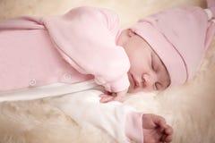 Fille nouveau-née dans une robe rose dormant sur la peau de moutons Photo stock