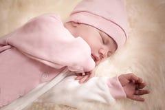 Fille nouveau-née dans une robe rose dormant sur la peau de moutons Image stock