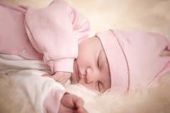 Fille nouveau-née dans une robe rose dormant sur la peau de moutons Photo libre de droits