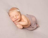 Fille nouveau-née de sommeil de sourire couverte de châle photographie stock libre de droits