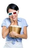 Fille observant le film 3D avec le bol de maïs éclaté Images stock