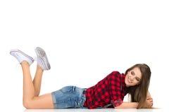 Fille occasionnelle se couchant sur un plancher et regardant loin Photographie stock libre de droits