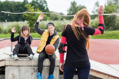 Fille ondulant au revoir au skatepark Photo stock