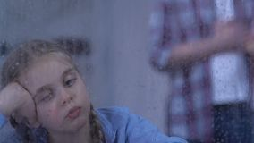 Fille orpheline regardant sur la pluie, famille adoptive se tenant derrière, espoir pour la nouvelle vie banque de vidéos