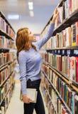 Fille ou femme heureuse d'étudiant avec le livre dans la bibliothèque Photos libres de droits