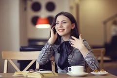 Fille parlant au téléphone dans un café Photos libres de droits
