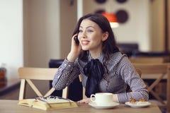 Fille parlant au téléphone dans un café Image stock
