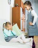 Fille parlant la petite soeur dans l'intérieur domestique photo libre de droits