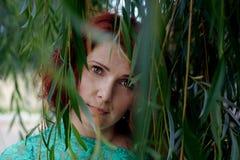 Fille parmi les feuilles vertes Images stock
