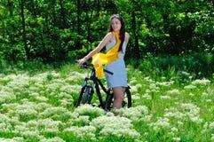 Fille parmi les fleurs sauvages sur un vélo Photos libres de droits