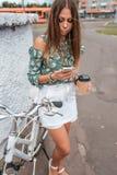 Fille pendant l'été dans la ville, à disposition téléphone par tasse de thé de café Le vélo blanc, indique la correspondance dans image stock