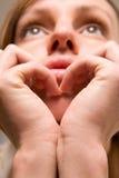 Fille pensive effectuant le signe de coeur Images libres de droits
