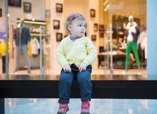 Fille perdue s'asseyant sur le banc dans le mail Image stock