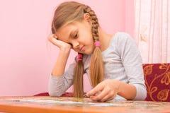 Fille peu fatigué rassemblant des puzzles de photo Images stock