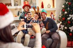 Fille photographiant des amis par le téléphone pour Noël Photo stock