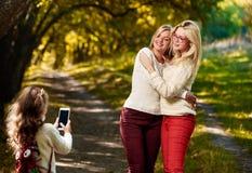 Fille photographiant des soeurs Photo libre de droits