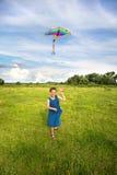 Fille pilotant un cerf-volant dans le domaine Photo stock