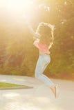 Fille Pin- sautant en parc au coucher du soleil Image libre de droits