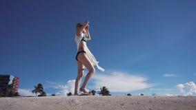 Fille, plage, mer, vent dans vos cheveux, fille dans le bikini marchant le long de la plage avec le sable banque de vidéos