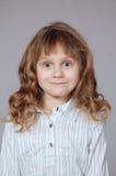 Fille pop-eyed de sourire mignonne avec le cheveu bouclé photos libres de droits