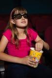 Fille portant les lunettes 3D tout en ayant des maïs éclatés pendant le film Photographie stock libre de droits