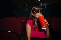Fille portant les lunettes 3D tout en ayant la boisson pendant le film Image libre de droits