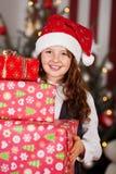 Fille portant une pile des cadeaux de Noël Photographie stock libre de droits