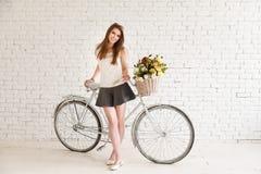 Fille posant à côté de sa vieille rétro bicyclette Image libre de droits