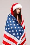 Fille posant avec le drapeau américain sur le plan rapproché gris de fond Image stock