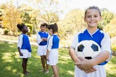 Fille posant avec son équipe de football à l'arrière-plan Photos stock