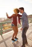 Fille posant sur la planche à roulettes pour le selfie Photos stock