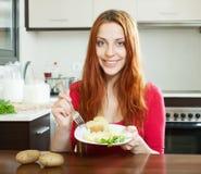 Fille positive en rouge mangeant des pommes de terre en robe de chambre Image libre de droits