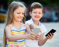 Fille positive et garçon regardant des téléphones portables en parc Image stock