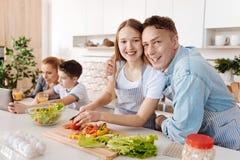 Fille positive faisant cuire avec son père dans la cuisine Photographie stock