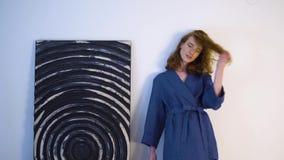 Fille positive gaie dans la robe bleue posant pour l'appareil-photo dans le studio de photo banque de vidéos