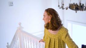 Fille positive gaie dans la robe jaune posant pour l'appareil-photo dans le studio de photo banque de vidéos