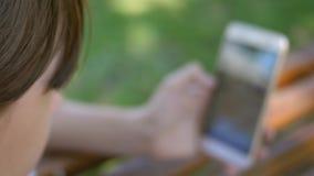 fille poussant des feuilles par l'instagram La belle fille ? l'aide d'un smartphone ?crit une lettre sur un banc dans un beau par banque de vidéos