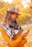 Fille près d'arbre d'automne avec le téléphone photo libre de droits