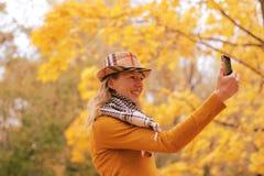 Fille près d'arbre d'automne avec le téléphone images stock