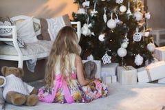 Fille près d'arbre de Noël avec des présents et des jouets, boîtes, Noël, nouvelle année, mode de vie, vacances, vacances, Santa  Photographie stock libre de droits